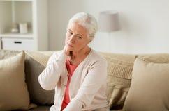 Femme supérieure souffrant de la douleur cervicale à la maison Photos stock