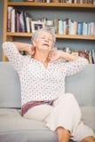 Femme supérieure souffrant de la douleur cervicale sur le sofa Image libre de droits