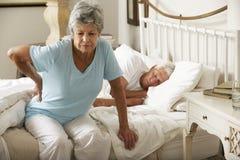 Femme supérieure souffrant de sortir de mal de dos du lit image stock