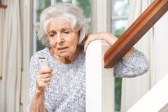 Femme supérieure souffrante employant l'alarme personnelle à la maison Image libre de droits