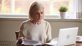 Femme supérieure soumise à une contrainte jugeant des papiers préoccupés avec les factures domestiques banque de vidéos