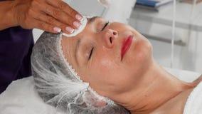 Femme supérieure souriant tandis que cosmetologist nettoyant son visage avec des protections de coton clips vidéos