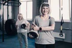 Femme supérieure sportive avec le tapis de yoga renonçant à des pouces Photographie stock libre de droits