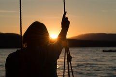 Femme supérieure sur l'oscillation avec le coucher du soleil Photo stock