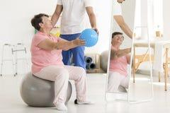 Femme supérieure sur la boule d'exercice Photo stock