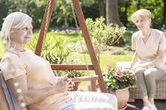 Femme supérieure sur la chaise accrochante dans le jardin avec le travailleur social image libre de droits