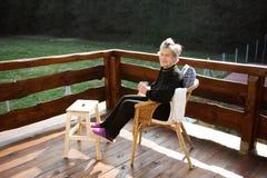 Femme supérieure sur la terrasse en bois, se reposant avec des pieds  Image stock