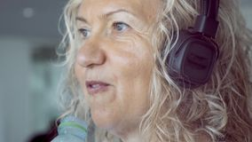 Femme supérieure sur le tapis roulant dans le gymnase écoutant la musique avec des écouteurs, plan rapproché banque de vidéos