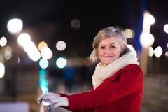 Femme supérieure sur une promenade dans la ville de nuit L'hiver Photo libre de droits