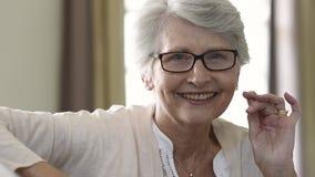 Femme supérieure tenant des lunettes avec l'humeur banque de vidéos