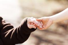 Femme supérieure tenant des mains avec le jeune gardien Image libre de droits