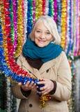 Femme supérieure tenant des tresses au magasin de Noël Image libre de droits