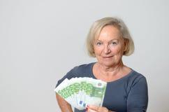 Femme supérieure tenant la fan des euros avec des pouces  Photo libre de droits