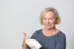 Femme supérieure tenant la fan des euros avec des pouces  Photographie stock