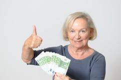 Femme supérieure tenant la fan des euros avec des pouces  Photos libres de droits