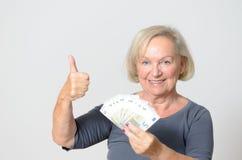 Femme supérieure tenant la fan des euros avec des pouces  Photos stock