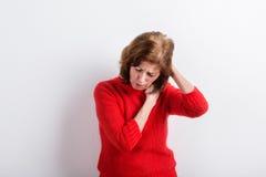 Femme supérieure tenant la tête, ayant le mal de tête Projectile de studio Image libre de droits