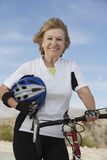 Femme supérieure tenant le casque et se tenant prêt la bicyclette Photos libres de droits
