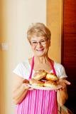 Femme supérieure tenant le plat avec des butées toriques Image libre de droits