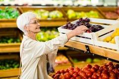 Femme supérieure tenant le sac avec la pomme Photos stock