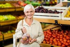 Femme supérieure tenant le sac avec la pomme Images libres de droits