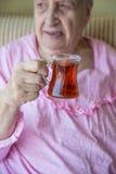 Femme supérieure tenant le thé Photos stock