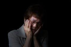 Femme supérieure tenant le visage tandis qu'en douleur sur le fond noir Photos stock