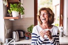 Femme supérieure tenant une tasse de café dans la cuisine Images stock