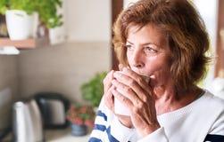 Femme supérieure tenant une tasse de café dans la cuisine Photo stock