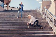 Femme supérieure tombant vers le bas les escaliers Photos libres de droits