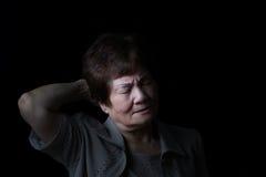 Femme supérieure touchant le dos de sa tête tandis qu'en douleur sur le blac Photos libres de droits