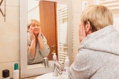 Femme supérieure touchant sa peau molle de visage, regardant dans le miroir à la maison image libre de droits