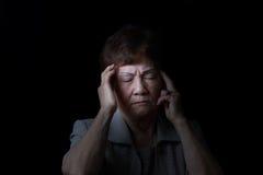 Femme supérieure touchant sa tête tandis qu'en douleur sur le fond noir Image stock
