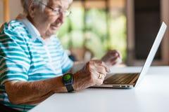 Femme supérieure très vieille à l'aide d'un ordinateur photo libre de droits