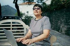 Femme supérieure travaillant sur l'ordinateur portable en café d'extérieur Photographie stock