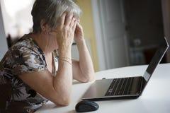 Femme supérieure travaillant sur son ordinateur portable dans sa cuisine Photo libre de droits