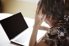 Femme supérieure travaillant sur son ordinateur portable dans sa cuisine Image libre de droits
