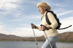 Femme supérieure trimardant près du lac Images libres de droits