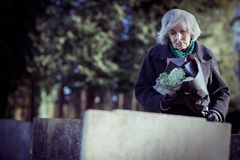 Femme supérieure triste avec des fleurs se tenant prêt la tombe Photographie stock