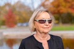 Femme supérieure utilisant les lunettes de soleil modernes à la mode Image stock