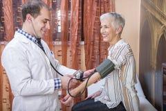 Femme supérieure vérifiant sa tension artérielle à la clinique photo stock