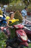 Femme supérieure vietnamienne avec les fleurs jaunes Photographie stock libre de droits