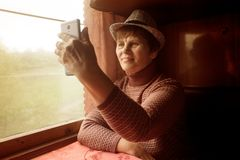 Femme supérieure voyageant sur le train et prenant le selfie au téléphone photos stock