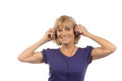 Femme supérieure 50-60years écoutant la musique avec l'écouteur stéréo Images stock