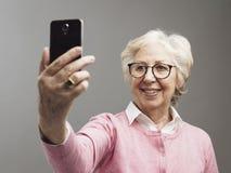 Femme sup?rieure heureuse prenant des selfies avec son smartphone photos libres de droits