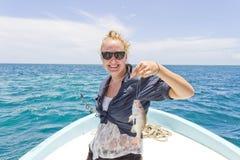 Femme supportant un poisson qu'elle a pêché Image stock