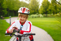 Femme supérieure active heureuse sur le vélo Images libres de droits
