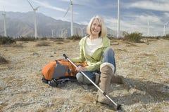 Femme supérieure avec augmenter Polonais et sac à dos au champ d'éoliennes Photographie stock