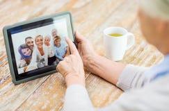 Femme supérieure avec la photo de famille sur l'écran de PC de comprimé Photo stock