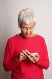 Femme supérieure confuse à l'aide du smartphone Photo stock